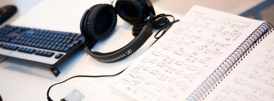 partitions, clavier et écouteurs sur un bureau